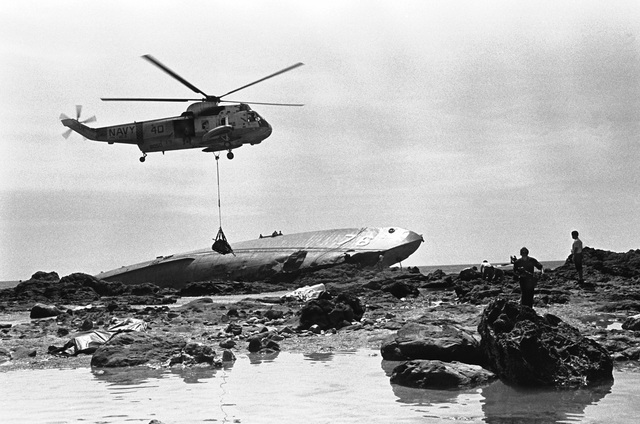 A right side view of an SH-3A Sea King helicopter, from Fleet Composite Squadron 5 (VC-5), as it airlifts bodies from near the beached and overturned Filipino frigate RPS DATU KALANTIAW (PS-76) during search and rescue (SAR) operations. The ship was overtaken by Typhoon Clara