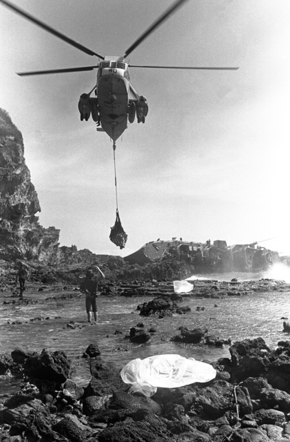 An underside view, looking toward the rear, of an SH-3A Sea King helicopter, from Fleet Composite Squadron 5 (VC-5), as it airlifts bodies from near the beached and overturned Filipino frigate RPS DATU KALANTIAW (PS-76) during search and rescue (SAR) operations. The ship was overtaken by Typhoon Clara