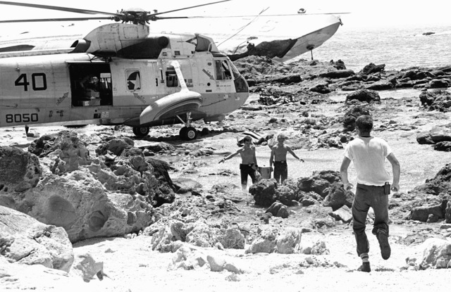 Crewmen from the ammunition ship USS MOUNT HOOD (AE-29) and an SH-3A Sea King helicopter, from Fleet Composite Squadron 5 (VC-5), participate in search and rescue (SAR) operations for the beached and overturned Filipino frigate RPS DATU KALANTIAW (PS-76). The ship was overtaken by Typhoon Clara