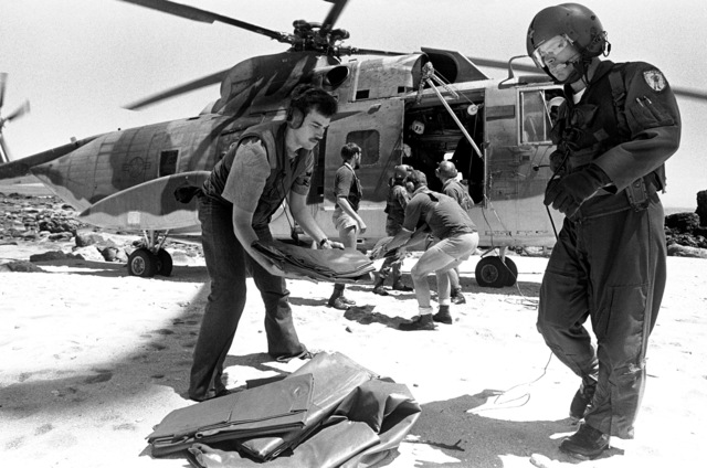 Crewmen from the ammunition ship USS MOUNT HOOD (AE-29) unload supplies from a U.S. Air Force helicopter during search and rescue operations for the beached and overturned Filipino frigate RPS DATU KALANTIAW (PS-76). The frigate was overtaken by Typhoon Clara
