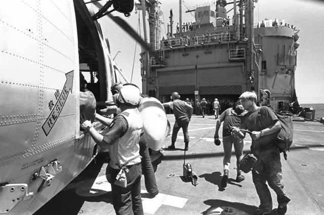 Crewmen load supplies aboard an SH-3A Sea King helicopter, from Fleet Composite Squadron 5 (VC-5), on the helicopter pad of the ammunition ship USS MOUNT HOOD (AE-29). The Sea King will carry the supplies to Calayan Island and participate in search and rescue (SAR) operations for the beached and overturned Filipino frigate RPS DATU KALANTIAW (PS-76). The frigate was overtaken by Typhoon Clara