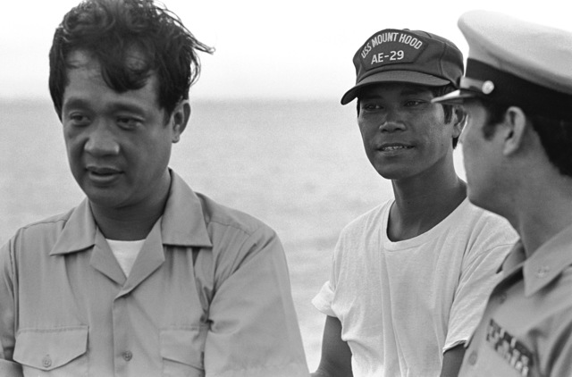 LT Luis D. Decanay, left, and CHIEF Electronics Technician (ETC) Francisco B. Nonisa, center, both of the Philippine navy and both survivors of the typhoon-damaged Filipino frigate RPS DATU KALANTIAW (PS-76), stand with a chief petty officer aboard the ammunition ship USS MOUNT HOOD (AE-29) while being transported from their wrecked ship on Calayan Island to manila. The two men were just picked up during search and rescue (SAR) operations
