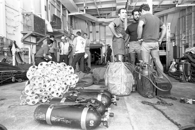 Members of Explosive Ordnance Disposal Team Detachment 21 (EOD Det. 21) wait with their gear for transportation from the ammunition ship USS MOUNT HOOD (AE-29) to Calayan Island to participate in search and rescue (SAR) operations for the typhoon-damaged Filipino frigate RPS DATU KALANTIAW (PS-76)