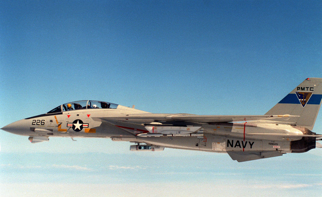 An air-to-air left side view of an F-14A Tomcat aircraft before launching an Advanced Medium Range Air-to-Air Missile (AMRAAM) over the Pacific Missile Test Center Range