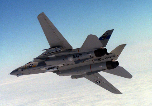 An air-to-air left underside view of an F-14A Tomcat aircraft before launching an advanced medium range air-to-air missile (AMRAAM) over the Pacific Missile Test Center Range