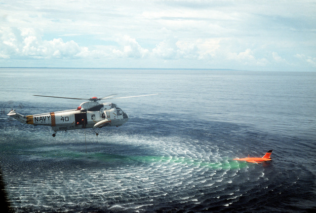 Air-to-air right side view of a Navy SH-3G Sea King helicopter from Fleet Composite Squadron Five (VC-5) approaching a BQM-34-S Firebee drone in the water. Note green marker dye emitted by the drone