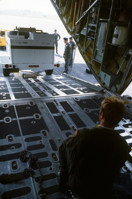 An interior view of a C-130 Hercules aircraft as a mobile Personnel Support for Contingency Operations (PERSCO) van's power generator is pulled aboard