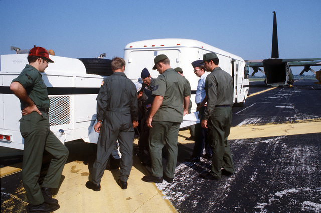 Measurements are taken before loading a mobile Personnel Support for Contingency Operations (PERSCO) van and generator aboard a C-130 Hercules aircraft