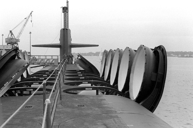A deck view, looking toward the bow, of the nuclear-powered fleet ballistic missile submarine OHIO (SSBN-726) with missile tubes open during precommissioning activities. The submarine, built by General Dynamics Corp., carries Trident C-4 (UGM-96) submarine-launched ballistic missiles (SLBM)