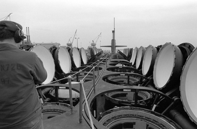 A deck view, looking toward the bow, of the nuclear-powered fleet ballistic missile submarine OHIO (SSBN-726) with a crewman on deck and open missile tubes during precommissioning activities. The submarine, built by General Dynamics Corp., carries Trident C-4 (UGM-96) submarine-launched ballistic missiles (SLBM)