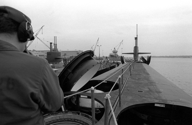 A deck view, looking toward the bow, of the nuclear-powered fleet ballistic missile submarine OHIO (SSBN-726) with a crewman on deck and some open missile tubes during precommissioning activities. The submarine, built by General Dynamics Corp., carries Trident C-4 (UGM-96) submarine-launched ballistic missiles (SLBM)