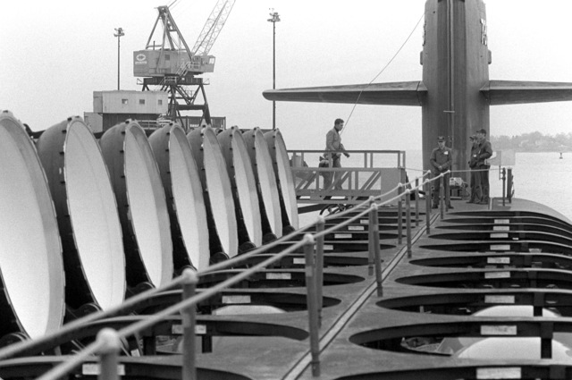 A deck view, looking toward the bow, of the nuclear-powered fleet ballistic missile submarine OHIO (SSBN-726) with missile tubes open and crewmen on her deck during precommissioning activities. The submarine, built by General Dynamics Corp., carries Trident C-4 (UGM-96) submarine-launched ballistic missiles (SLBM)