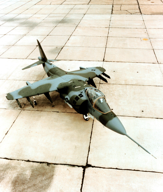 A high angle right front view of a Marine AV-8B Harrier II aircraft parked on the flight line