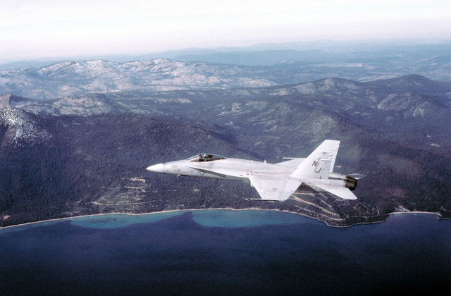 A left side view of an F/A-18A Hornet aircraft from Fighter Attack Squadron 125 (VFA-125) in flight over Lake Tahoe