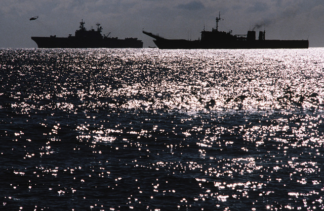 A silhouetted port beam view of the amphibious assault ship USS SAIPAN (LHA-2) and the tank landing ship USS BARNSTABLE COUNTY (LST-1197) underway during Exercise Crisex '81
