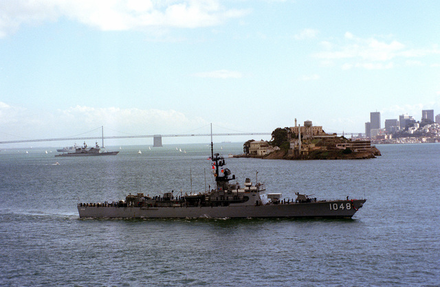 A starboard beam view of the frigate USS SAMPLE (FF-1048) underway during Fleet Week activities. Visible in the background are the San Francisco-Oakland Bay Bridge, Alcatraz Island, and the San Francisco skyline