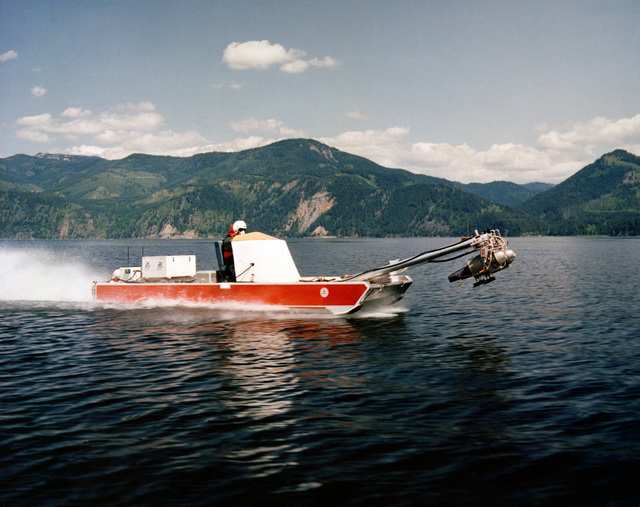 A starboard view of a manually driven, scaled-down version of a power-augmented ram landing craft (PARLAC) underway during research and development testing. The port engine of the PARLAC is elevated to provide cushion lift, resulting in increased speed and shore-landing capability