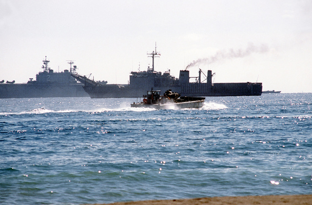 A utility landing craft carrying an M-60 tank approaches the tank landing ship USS BARNSTABLE COUNTY (LST-1197) during Exercise Crisex '81. The amphibious assault ship USS SAIPAN (LHA-2) is also visible in the background