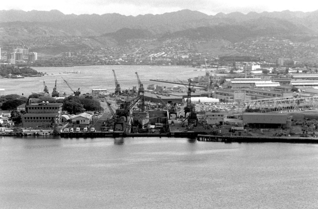 A view of the cranes and a dry docked ship at the naval shipyard with the USS ARIZONA MEMORIAL visible in the background, left, near Ford Island