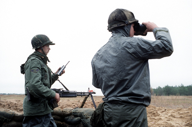 A1C Jeffrey Ballou and SSGT Steve Geist keep watch at a flight line security post during exercise Bold Eagle '82