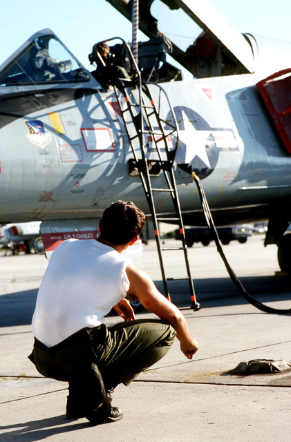 AIRMAN First Class (A1C) Paul Pepard and A1C Kevin Curran work on an F-106 Delta Dart aircraft to prepare for flight during exercise BOLD EAGLE '82