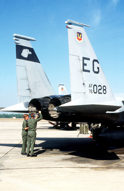 AIRMAN First Class (A1C) Steve Genord and A1C Dan Alverson, 60th Tactical Fighter Wing, check engine exhaust of an F-15 Eagle during exercise BOLD EAGLE '82