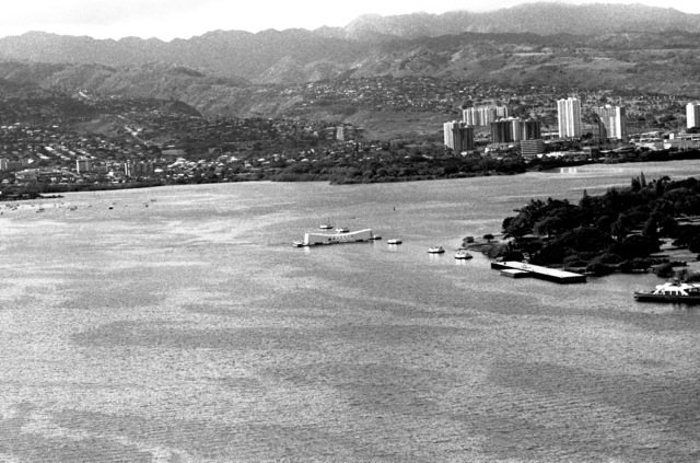 An aerial view of the USS ARIZONA MEMORIAL with Ford Island to the left and Aiea in the background
