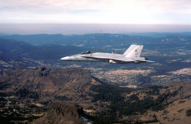 An air-to-air left side view of an F/A-18A Hornet aircraft from Fighter Attack Squadron 125 (VFA-125) over Lake Tahoe