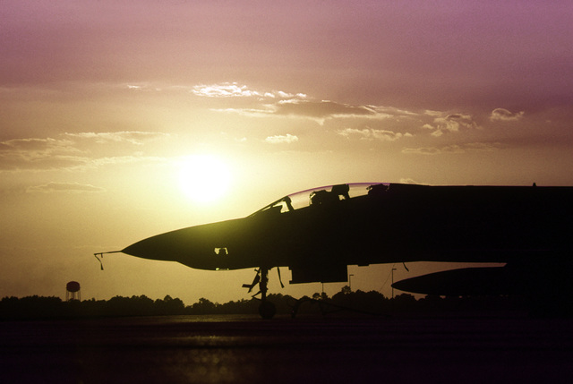 An F-4E Phantom II aircraft is silhouetted against the orange sky while parked on the flight line during exercise PHOTO Finish '81