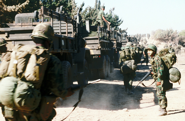 Army personnel from Fort Ord, California, move in formation along a dirt road while Marine Amphibious Service Support Group 32 passes in a convoy, during Exercise Crisex '81