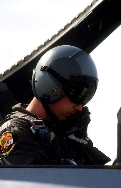 Captain Lee Halverson prepares for flight in the cockpit of his F-16 Fighting Falcon aircraft during exercise BOLD EAGLE '82
