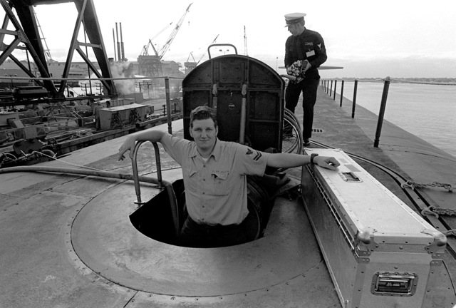 Electronics Technician 2nd Class (Submarines) (ET2) M. Pittinger, in the hatchway, loads equipment aboard the nuclear-powered ballistic missile submarine OHIO (SSBN-726) during precommissioning preparations. The submarine was built by General Dynamics Corp