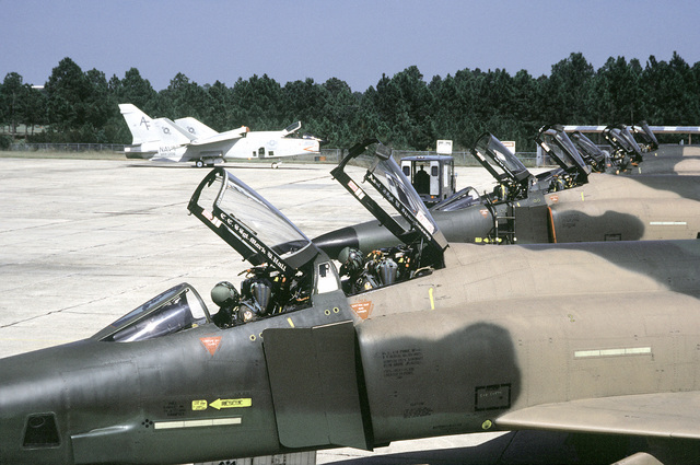 F-4E Phantom II aircraft on the flight line during exercise PHOTO Finish '81. In the background are two Navy RF-8G Crusader aircraft being prepared for flight