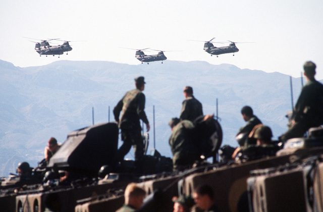 Four CH-47 Sea Knight helicopters fly overhead as Marines from the 1ST Plt., Co. D, 2nd Assault Amphibious Bn., Camp Lejeune, North Carolina, bring troops ashore on LVTP-7 tracked landing vehicles during Exercise Crisex '81