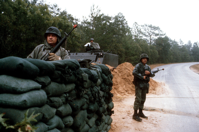 Personnel armed with M16 rifles guard the entry control point to Auxiliary Field One, during exercise BOLD EAGLE '82