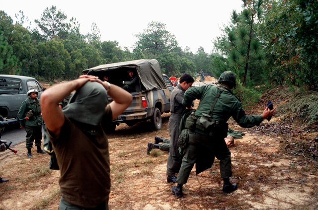 Prisoners of war are searched for weapons at the entry control point of Auxiliary Field One, during exercise BOLD EAGLE '82