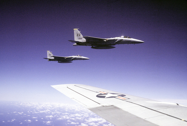 Right side air-to-air view of two F-15 Eagle aircraft from the 12th Tactical Fighter Wing, seen from another F-15 (wing visible in foreground). The aircraft are en route to Kadena Air Base, Okinawa at the conclusion of exercise Kangaroo '81