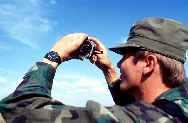 SENIOR AIRMAN James Harrel takes a wind reading with a Brunton's compass before he gives clearance for a jump to take place during exercise BOLD EAGLE '82