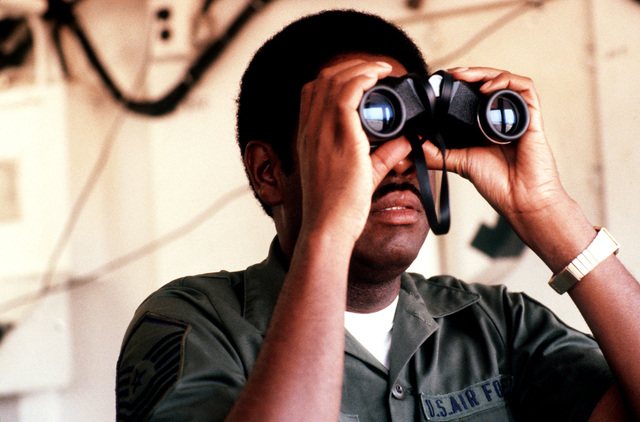 SENIOR MASTER Sergeant James R. Neely, 437th Military Air Wing, is looking for aircraft, through binoculars, from his position at the Airlift Control Element building during exercise BOLD EAGLE '82