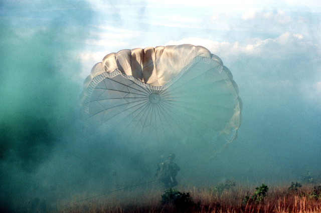 SENIOR MASTER Sergeant Tom Allen, 317th Tactical Air Wing, parachutes into the ground smoke, near the impact point, during exercise BOLD EAGLE '82
