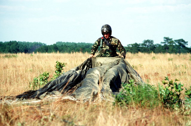 SENIOR MASTER Sergeant Tom Allen, 317th Tactical Air Wing, retrieves his parachute, after landing near the impact point, during exercise BOLD EAGLE '82