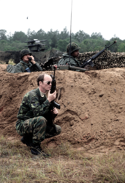 SRA Joseph Conner, 147th Security Police Fleet, Army SSGT James Stanford and Army CPL Kevin Lambright, 24th Infantry Division, watch for enemy aircraft at a security outpost during exercise Bold Eagle '82. The men are armed with M-16 rifles