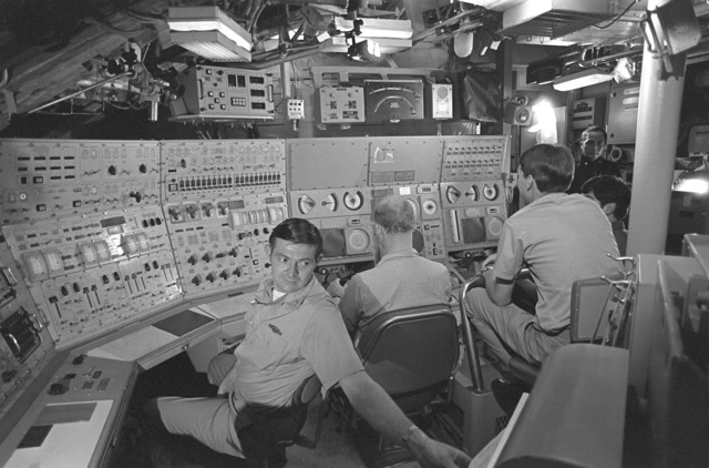 Three crewmen in the control room simulate diving operations during precommissioning activities aboard the nuclear-powered ballistic missile submarine OHIO (SSBN-726). From left, CHIEF Machinist's Mate S. I. Brown, CHIEF of Watch; SA W. L. Roberts, Stern Planesman; and ENS P. Price, diving officer