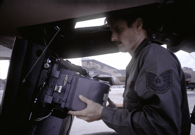 TSGT Glenn Farquhar loads film into camera equipment installed on an F-4 Phantom II aircraft prior to a mission during Exercise PHOTO Finish '81