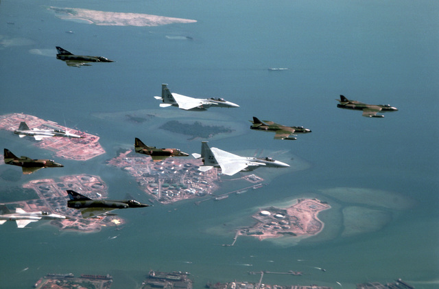 Two F-15 Eagle aircraft, center, from the 12th Tactical Fighter Wing; Royal Singapore Air Force (RSAF) Hunters, A-4s and F-5s; and Royal Australian Mirage aircraft fly in a 10-ship formation during a short operation with the RSAF at the completion of Exercise Kangaroo '81