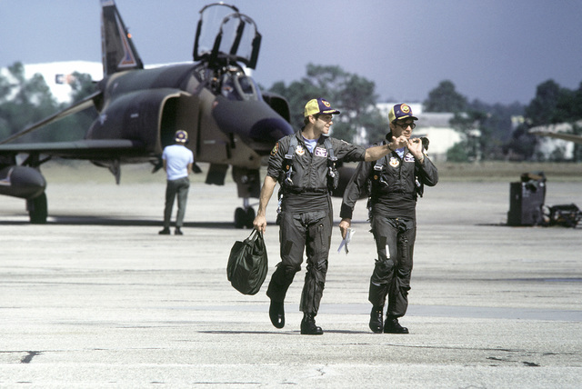 Two pilots walk off the flight line upon returning from a mission during exercise PHOTO Finish '81. AN F-4E Phantom II aircraft is parked in the background