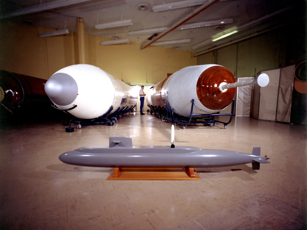 A view of a mock-up of a Trident I C-4 missile, right, and its predecessor, the Poseidon C-3 missile. The Trident is used on the nuclear-powered fleet ballistic missile submarine. In the foreground is a model of the nuclear-powered fleet ballistic missile submarine USS ULYSSES S. GRANT (SSBN-631) showing a simulated launching of a Poseidon missile