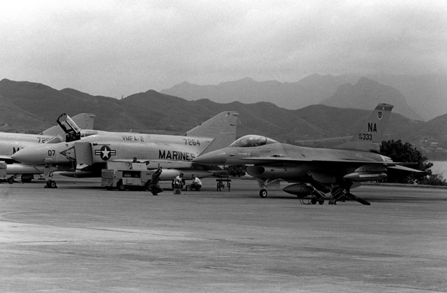 An Air Force F-16A Fighting Falcon aircraft is being directed by a ground crewman and is parked next to two Marine F-4 Phantom II aircraft. The F-16A is from the 428th Tactical Fighter Squadron located at Nellis Air Force Base, Nev., and is here to fly with Marine F-4 Phantom II aircraft in support of Hawaii-based Army units. The event is a Joint Chiefs of STAFF exercise, which will last for one month (Oct. 2 - Nov. 2, 1981)