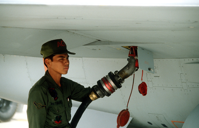 An airman refuels an F-16 Fighting Falcon aircraft on the flight line