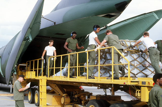Ground crewmen load F-16 Fighting Falcon aircraft spare parts onboard a C-141 Starlifter aircraft